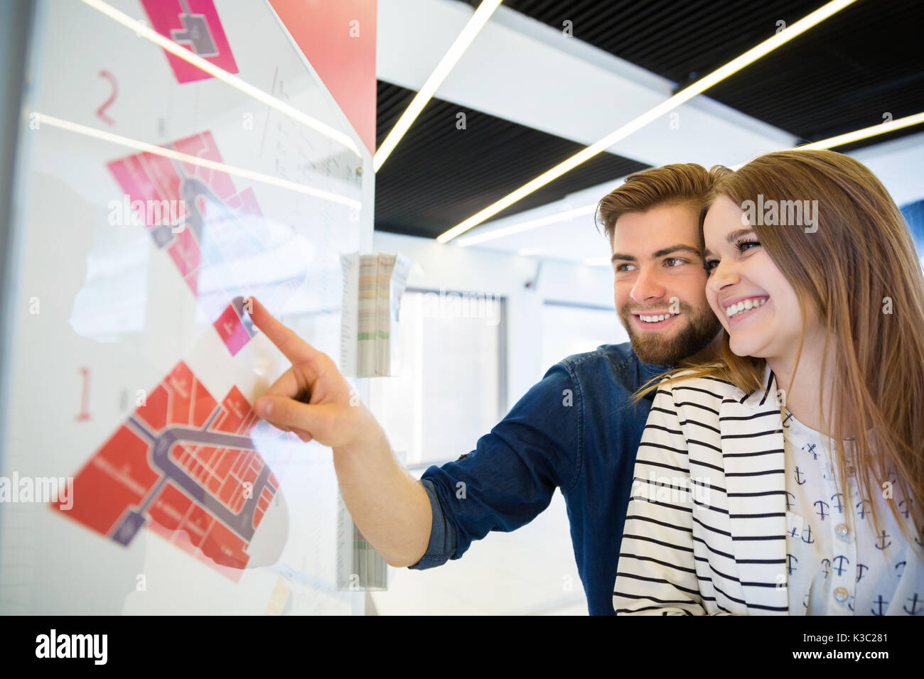 A photo of young, happy couple at the mall. They're checking out how to get to the shop. - Stock Image