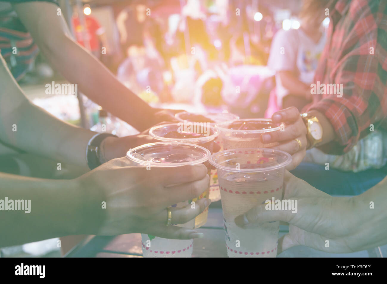 Friends clinking glasses above table.People holding glasses. cheering and celebration concept. - Stock Image