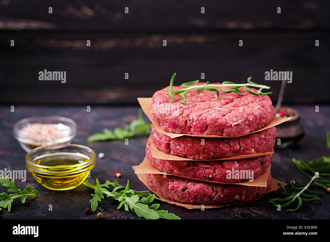 Fresh raw homemade minced beef steak burger with spices on black background - Stock Image