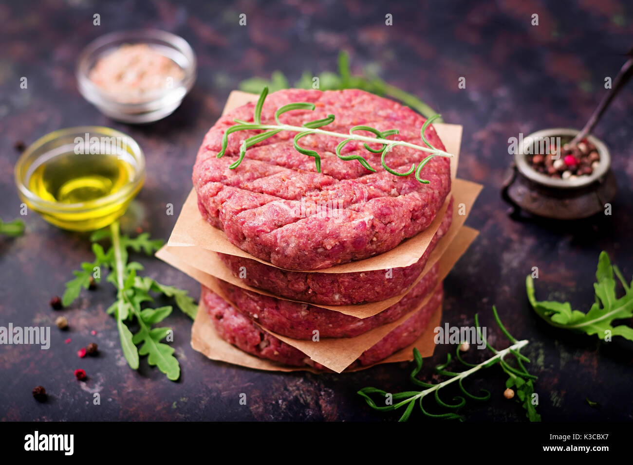 Fresh raw homemade minced beef steak burger with spices on black background Stock Photo