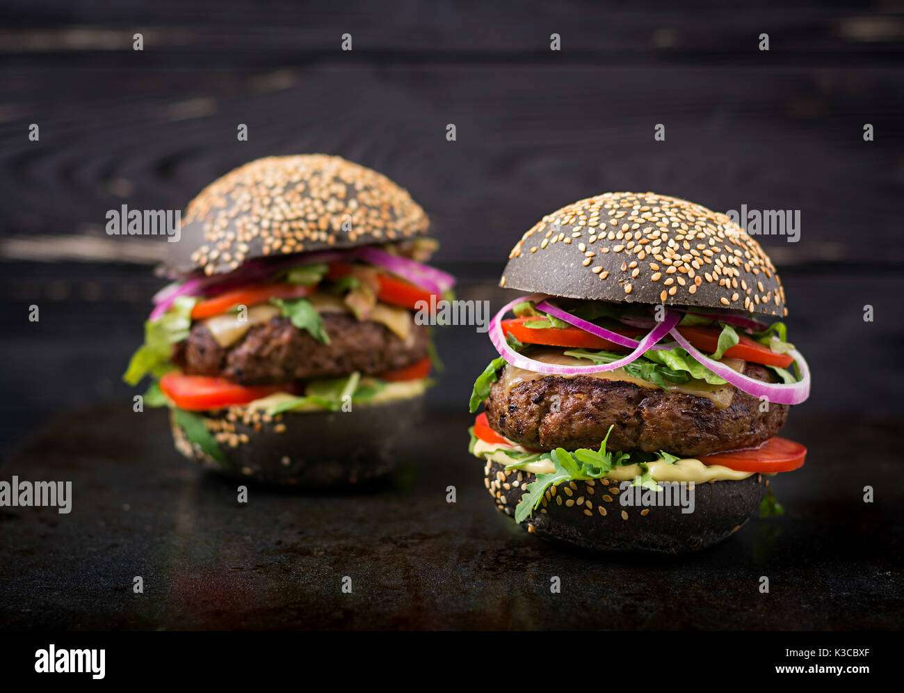 Black big sandwich -  black hamburger with juicy beef burger, cheese, tomato,  and red onion on black background - Stock Image