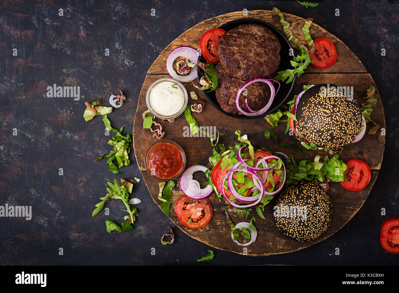 Black big sandwich -  black hamburger with juicy beef burger, cheese, tomato,  and red onion on black background Stock Photo