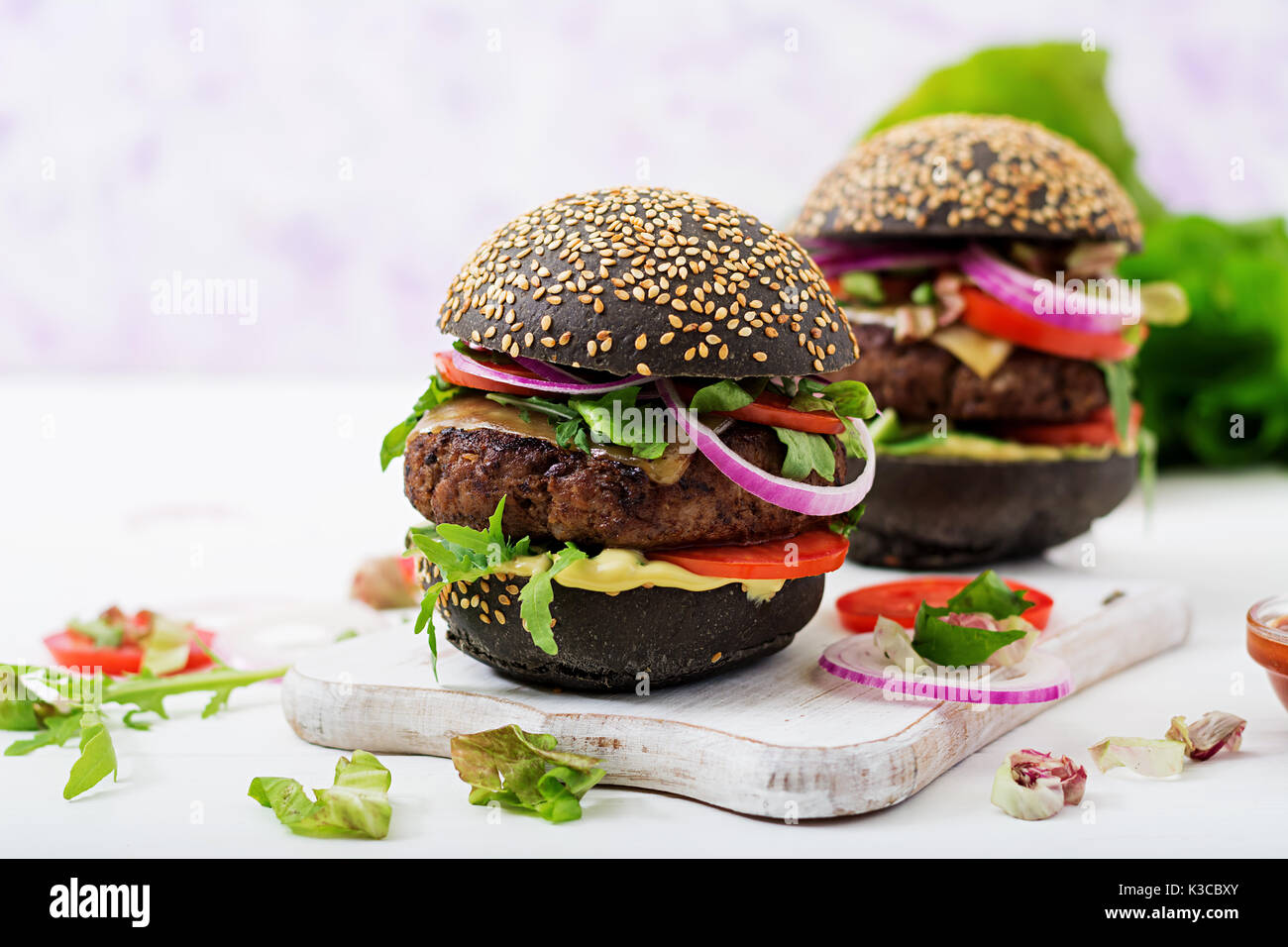 Black big sandwich -  black hamburger with juicy beef burger, cheese, tomato,  and red onion on light background. - Stock Image