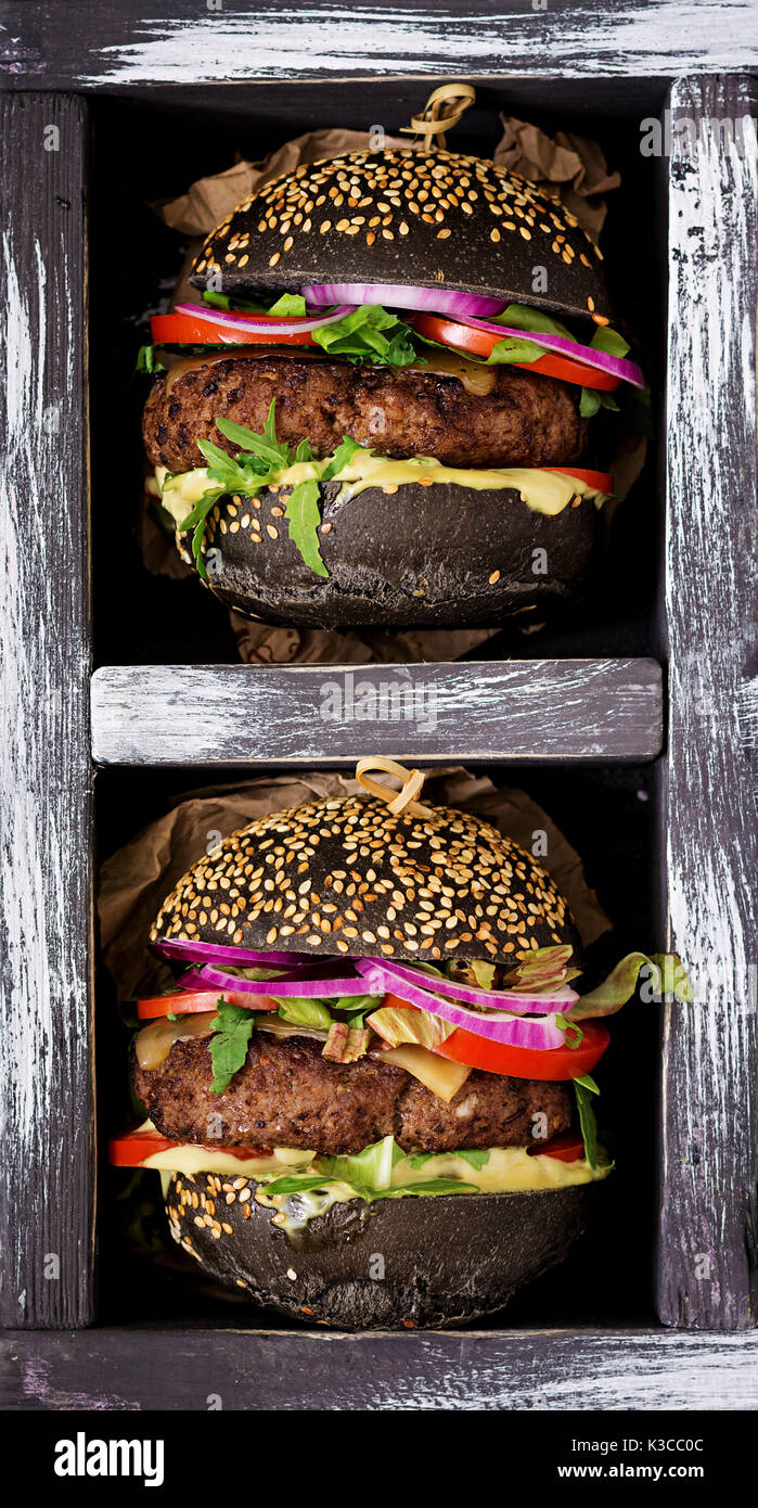 Black big sandwich -  black hamburger with juicy beef burger, cheese, tomato,  and red onion in box on black background.  Flat lay. Top view - Stock Image