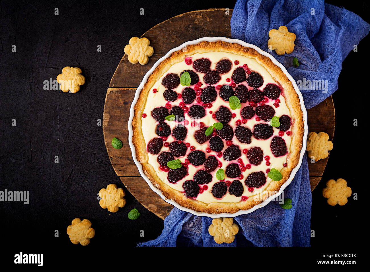 Tart with blackberry and cheesecake cream decorated with mint leaves. Top view. Flat lay - Stock Image