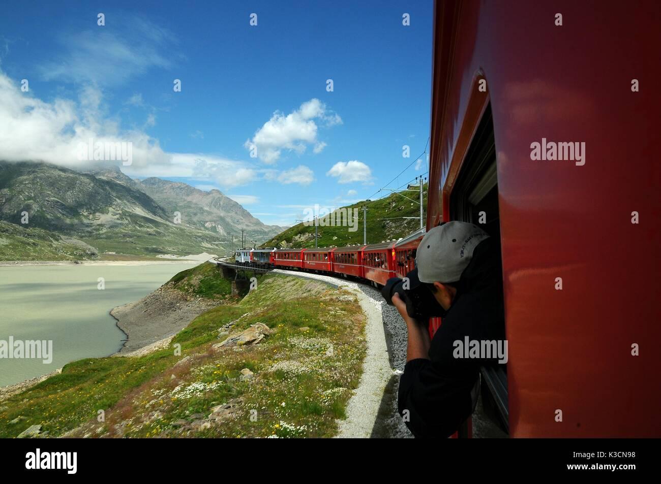 Famous red alpine train Bernina Express from St.Moritz to Tirano passing the Blanc Lake at Bernina Pass in Switzerland - Stock Image
