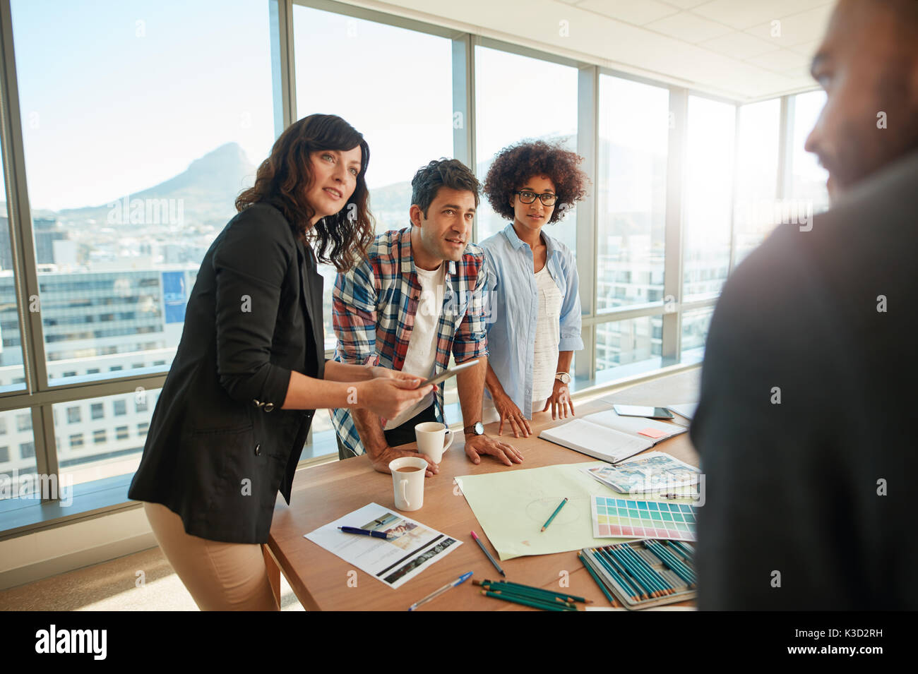 Group of young designer working together on project. Team brainstorming over new designs in meeting  room. - Stock Image
