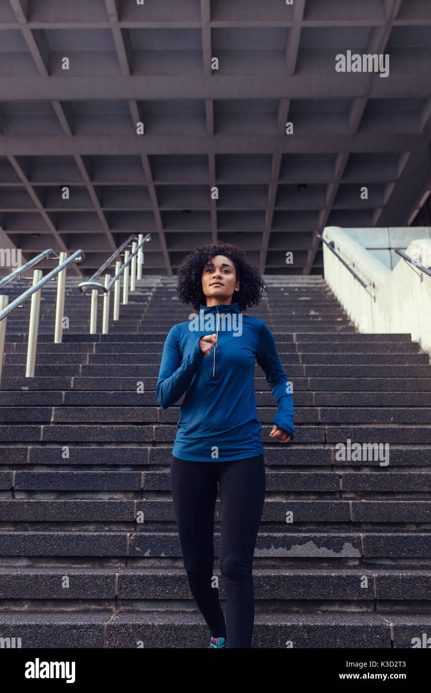 Woman in tracksuit running in city. Woman athlete climbing down stairs as part of her physical training. - Stock Image