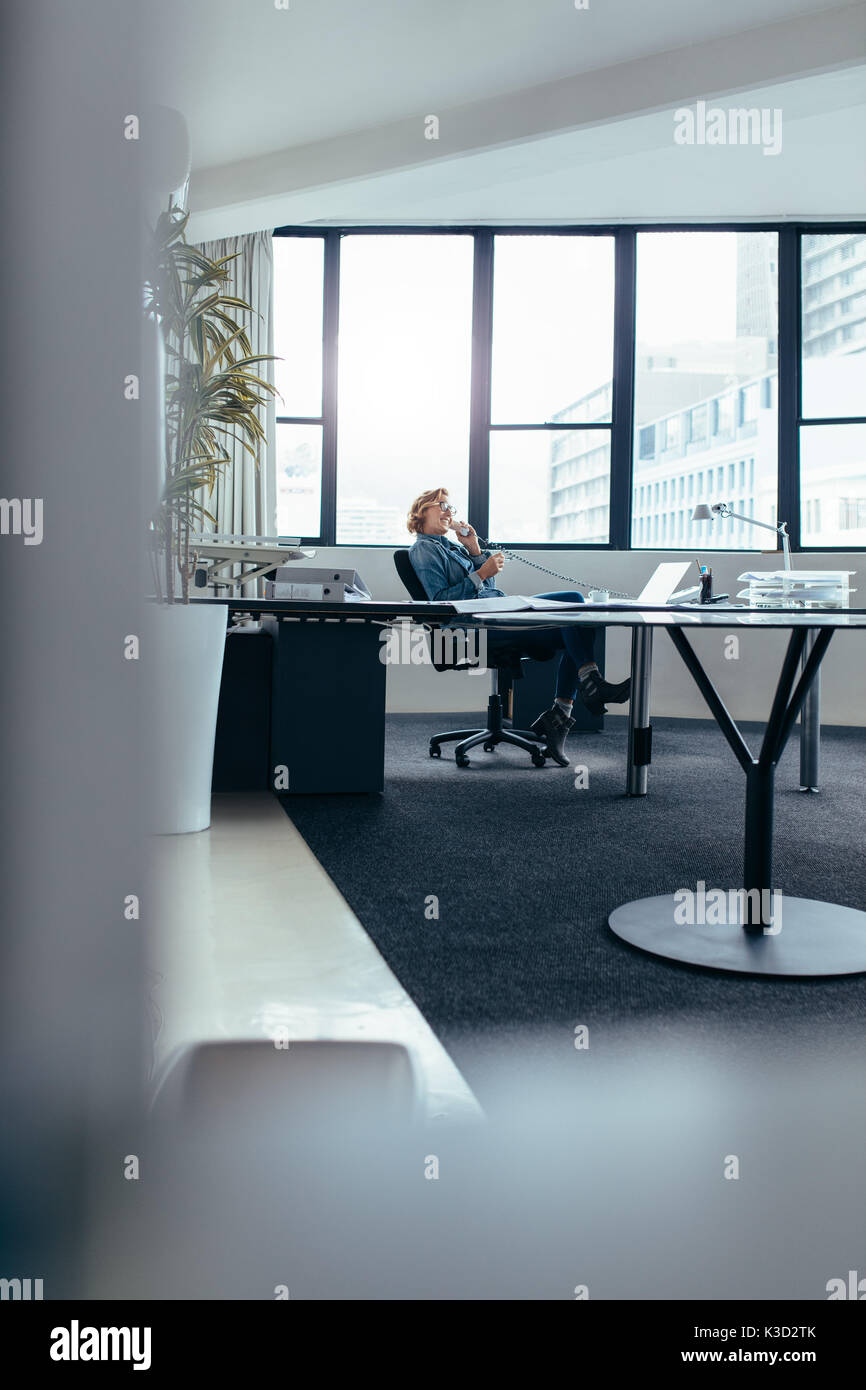Businesswoman sitting in office and talking on landline phone. Young woman using mobile phone in office. - Stock Image