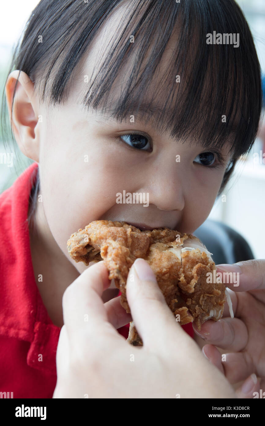 Asian Chinese mother and daughter eating fried chicken at indoor restaurant - Stock Image