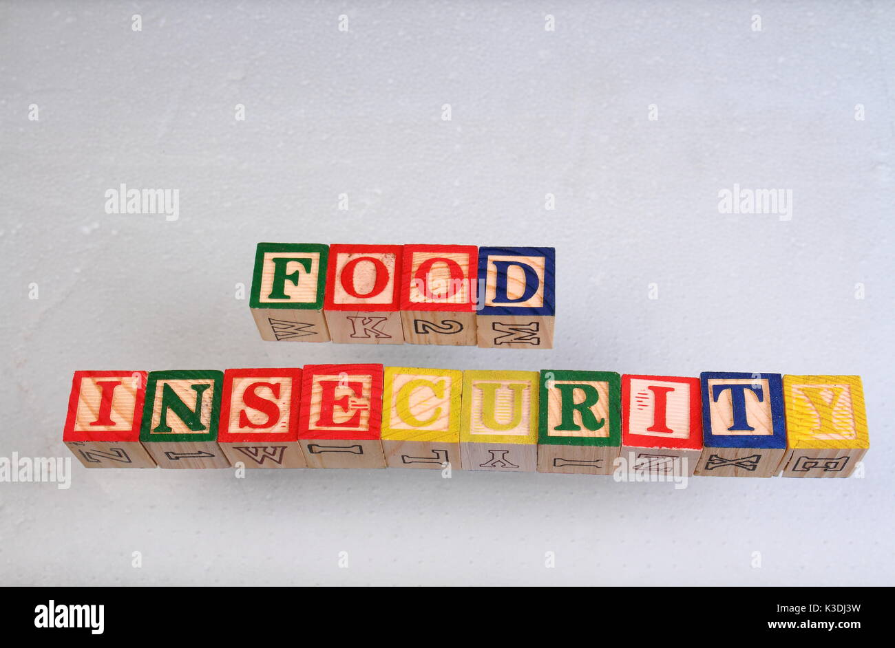 The term food insecurity displayed visually on a white background using colorful wooden toy blocks in landscape format with copy space - Stock Image