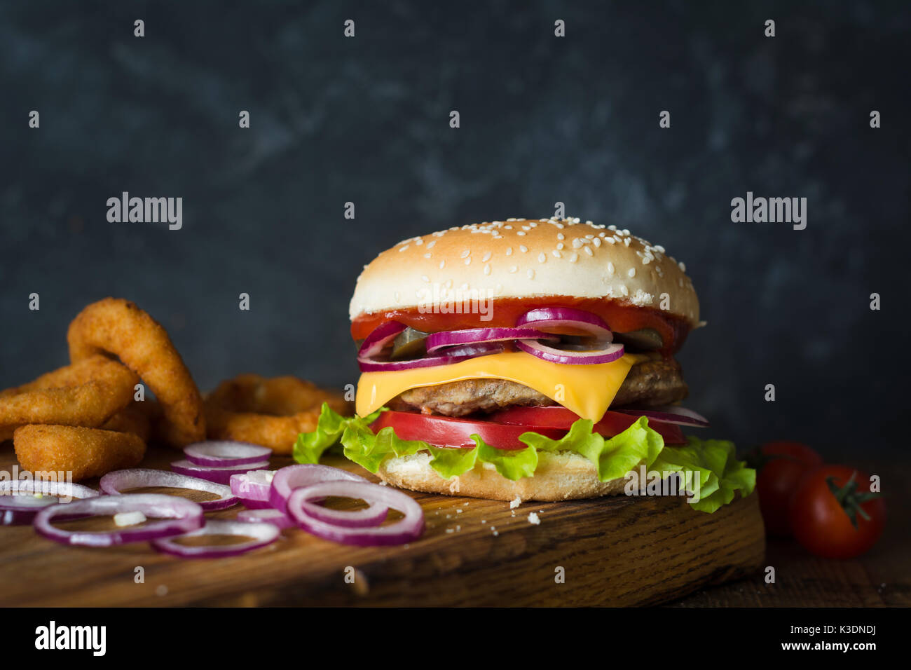 Cheeseburger and onion rings on wooden cutting board over dark background. Closeup view, selective focus. Fast food concept - Stock Image