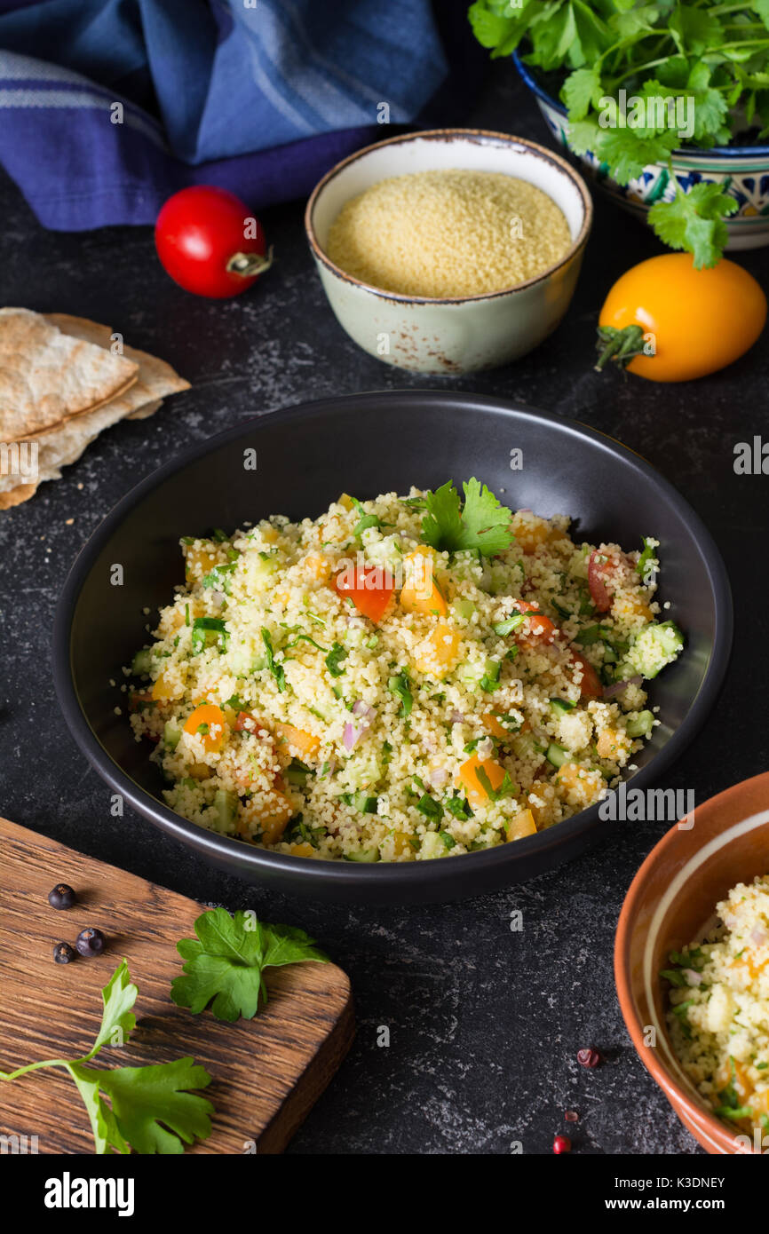 Lebanese arabic cuisine: healthy delicious salad with cous cous, fresh vegetables and greens called Tabbouleh in black bowl. Authentic cuisine - Stock Image