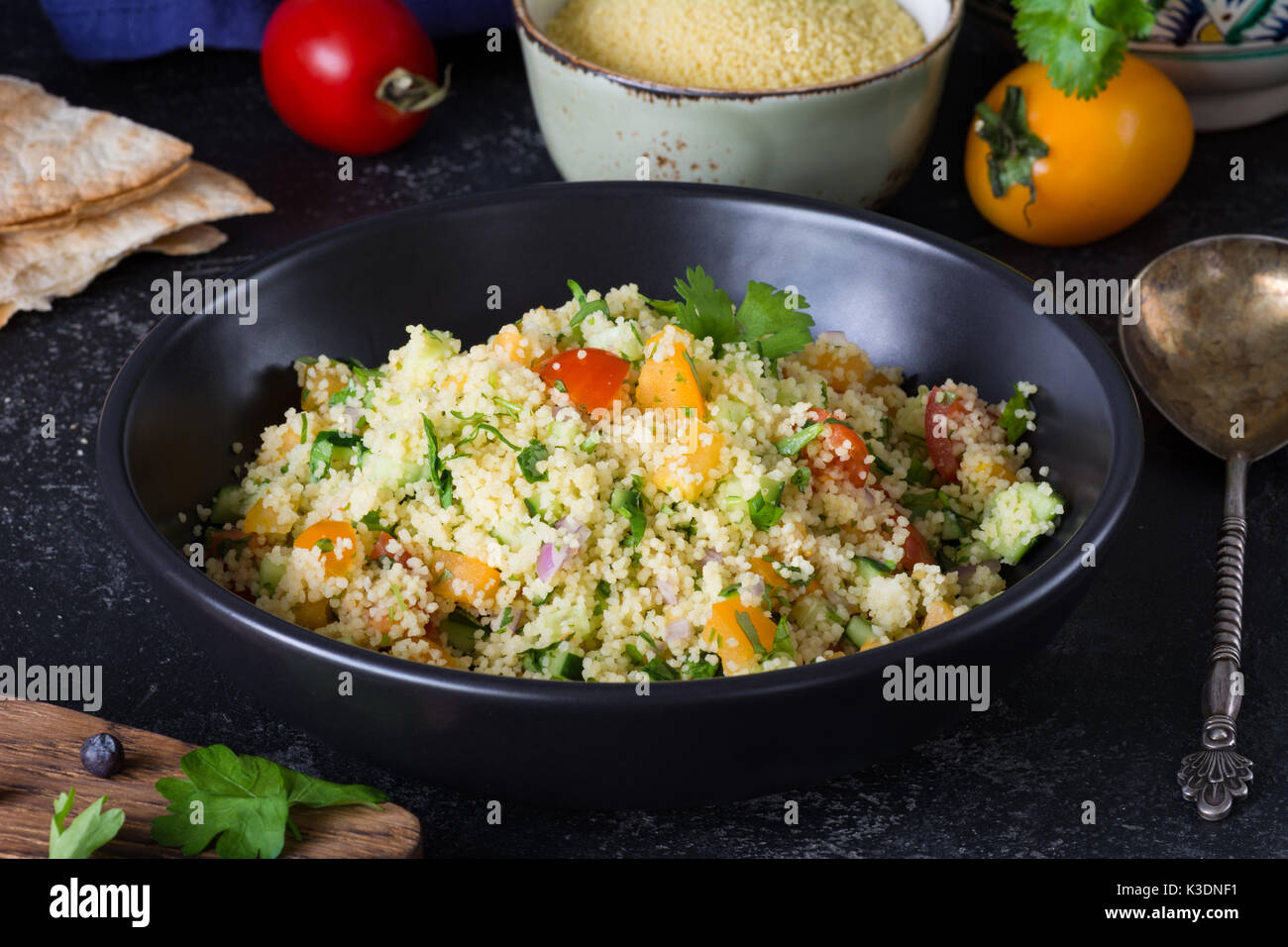 Lebanese arabic cuisine: healthy delicious salad with cous cous, fresh vegetables and greens called Tabbouleh in Stock Photo