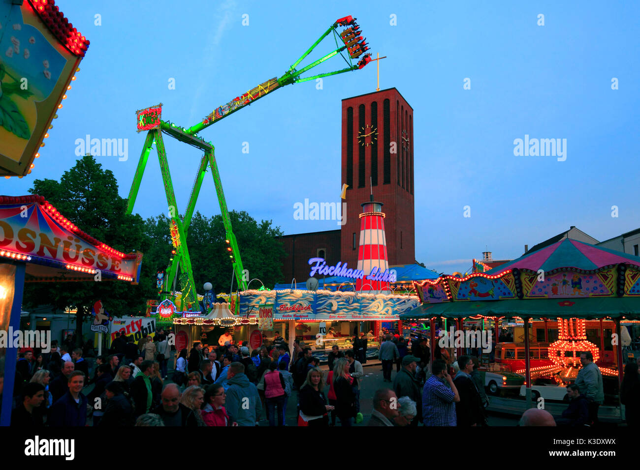 Sterkrader Fronleichnamskirmes (fair), fairground ride in front of the steeple of the Propsteikirche Saint Clemens Stock Photo
