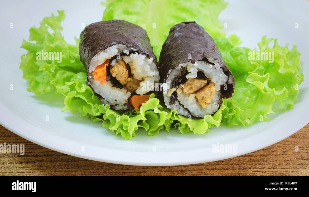 Japanese Cuisine, Traditional Vagetarian Japanese Rice Maki Sushi Roll Stuff with Tofu and Carrot Wrapped in Nori Seaweed Served on Green Oak. - Stock Image