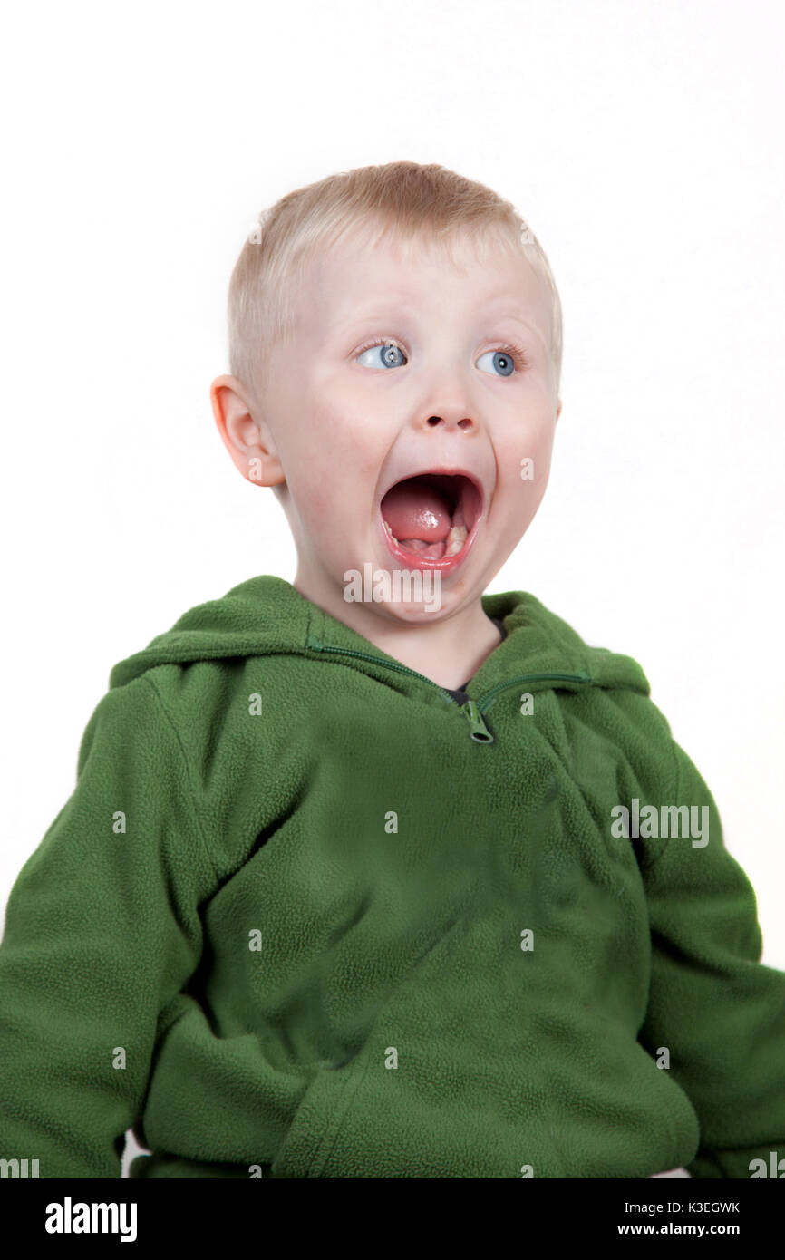 Wide eyed open mouthed smiling boy - Stock Image