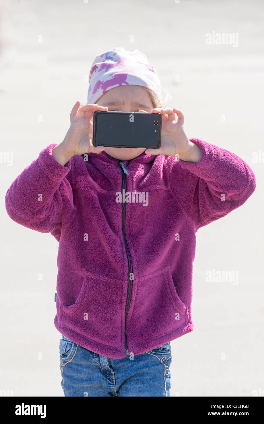 little girl takes a picture with a mobile phone - Stock Image