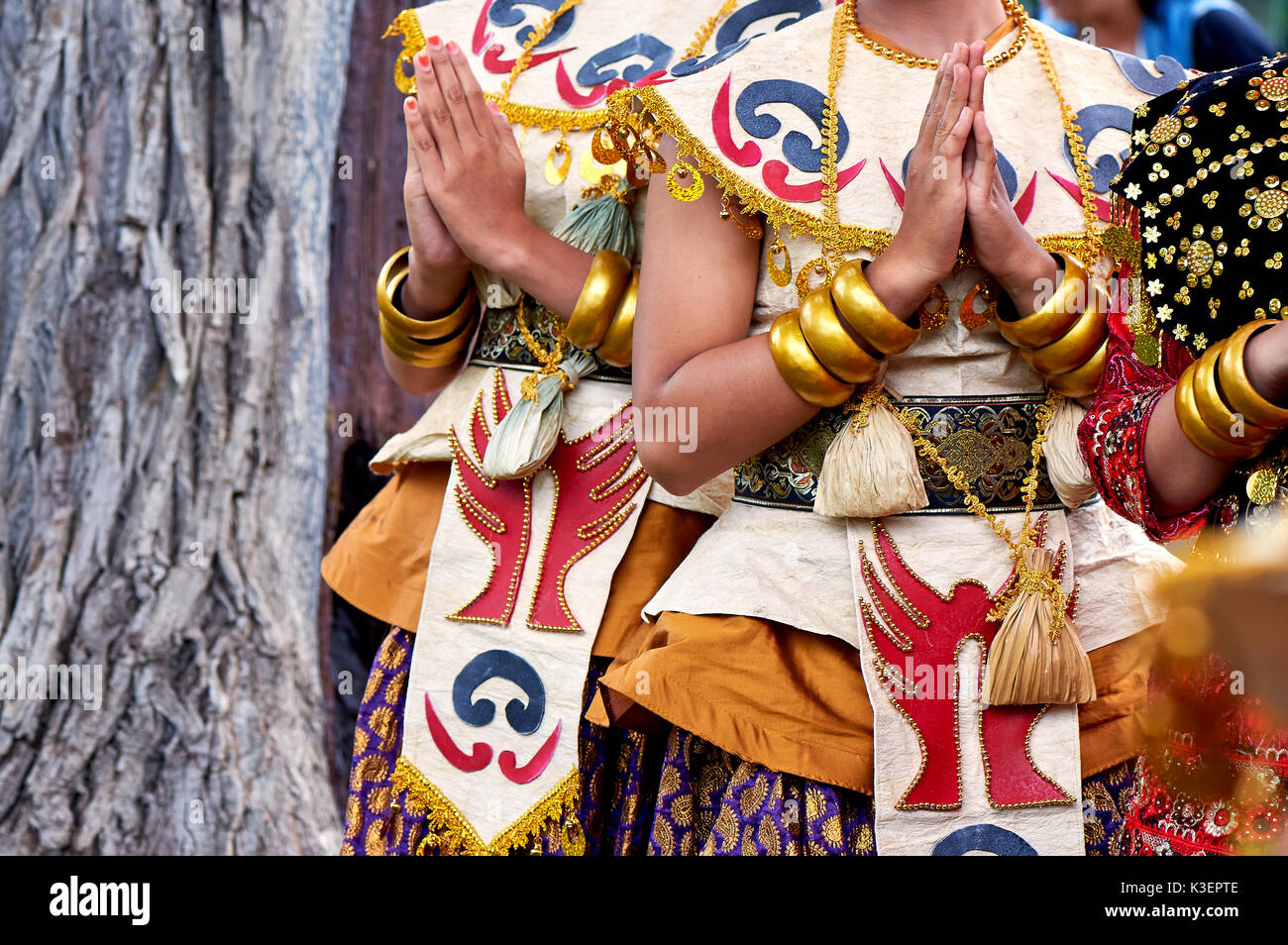 Indonesian national costume,hands in gold bracelets. Bright colors - Stock Image