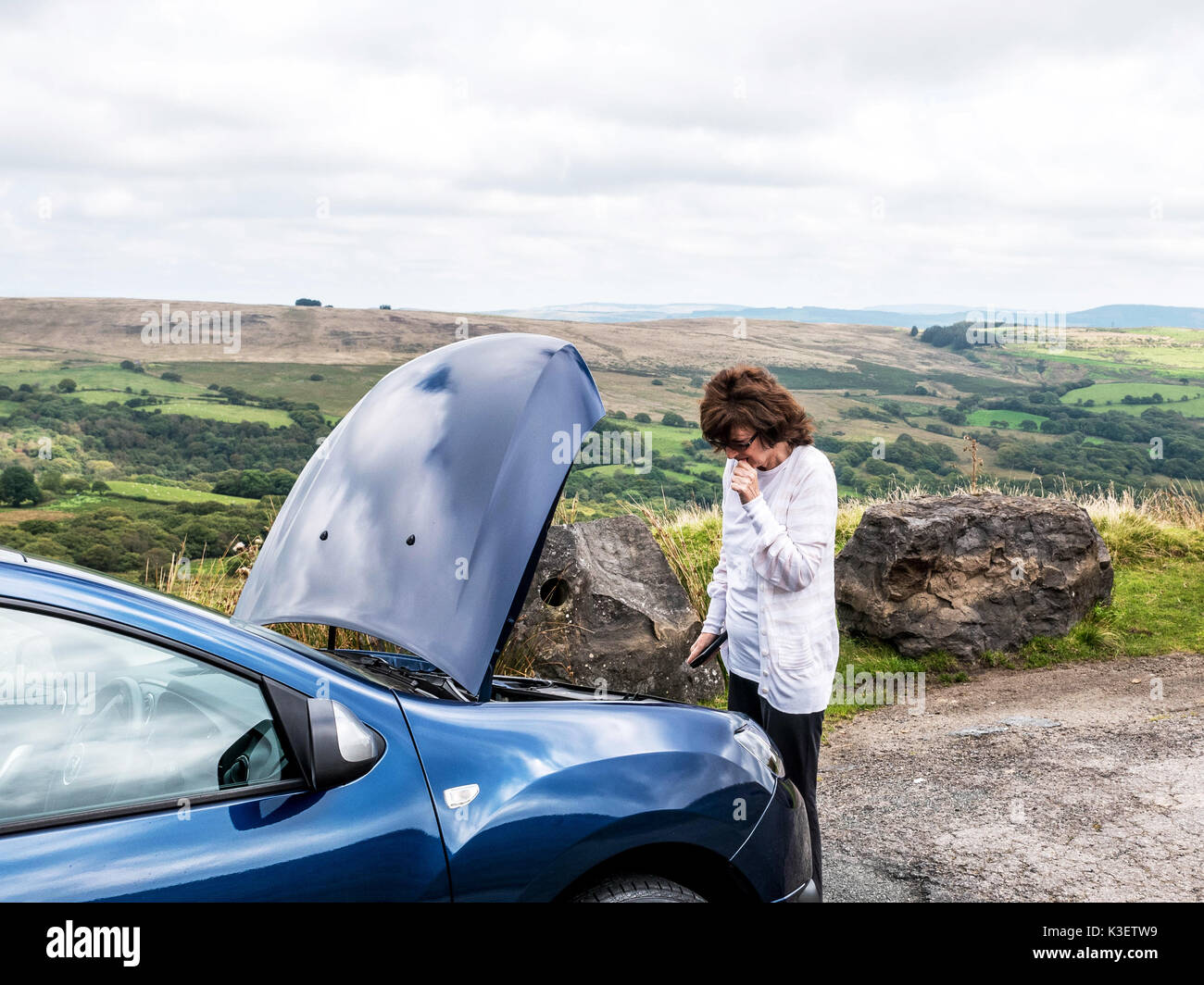 Mature lady looking at car engine after car breakdown in remote countryside. - Stock Image