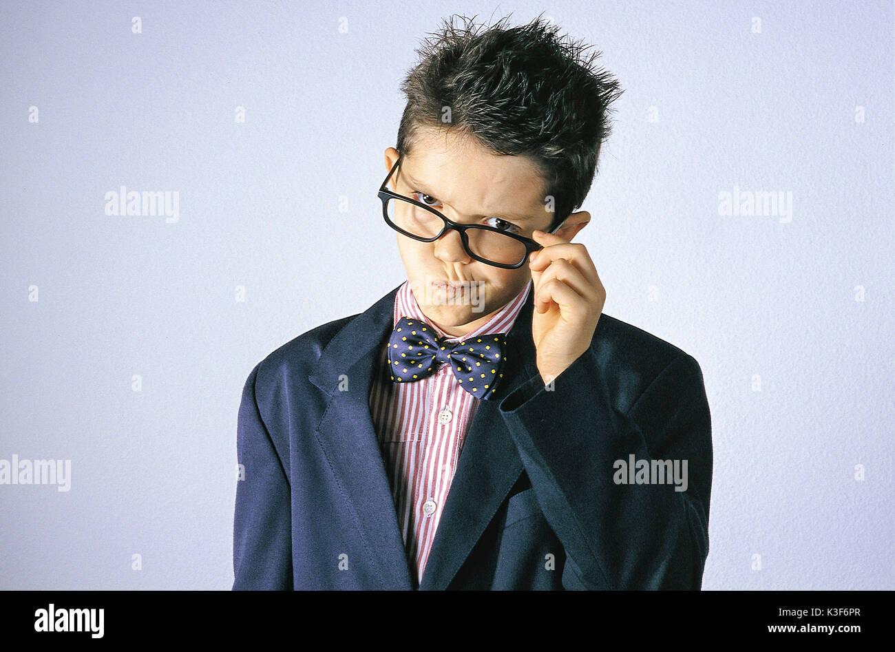 Small boy with bow tie touches with his hand the glasses frame and pulls his mouth - Stock Image