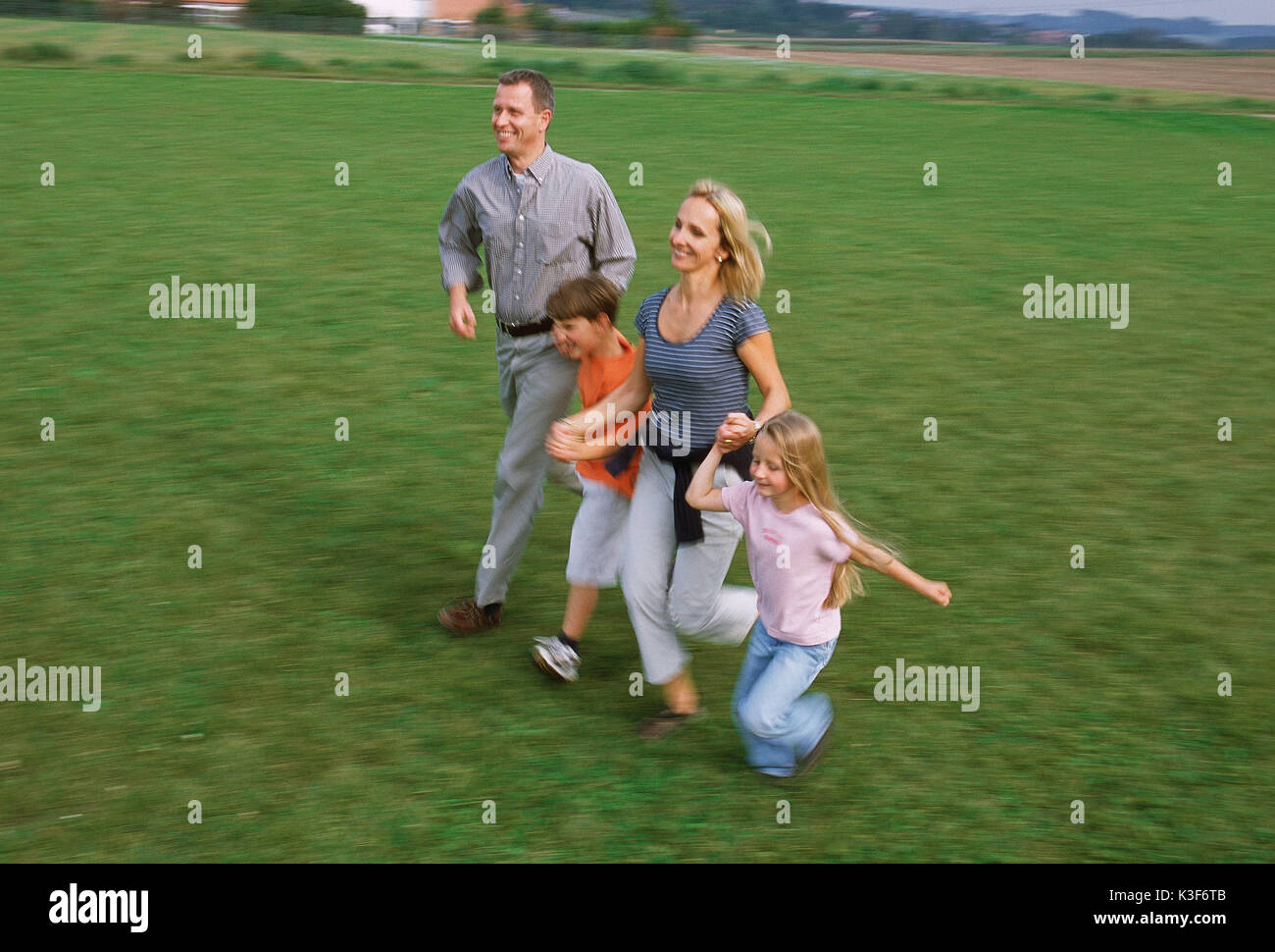 Young family runs hand in hand over a meadow - Stock Image