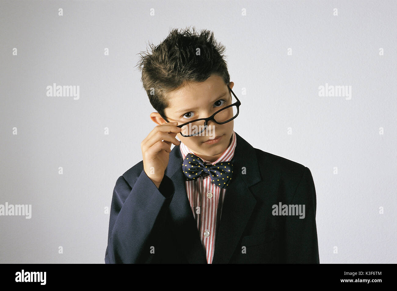 Small boy with bow tie grabs himself to the frame - Stock Image