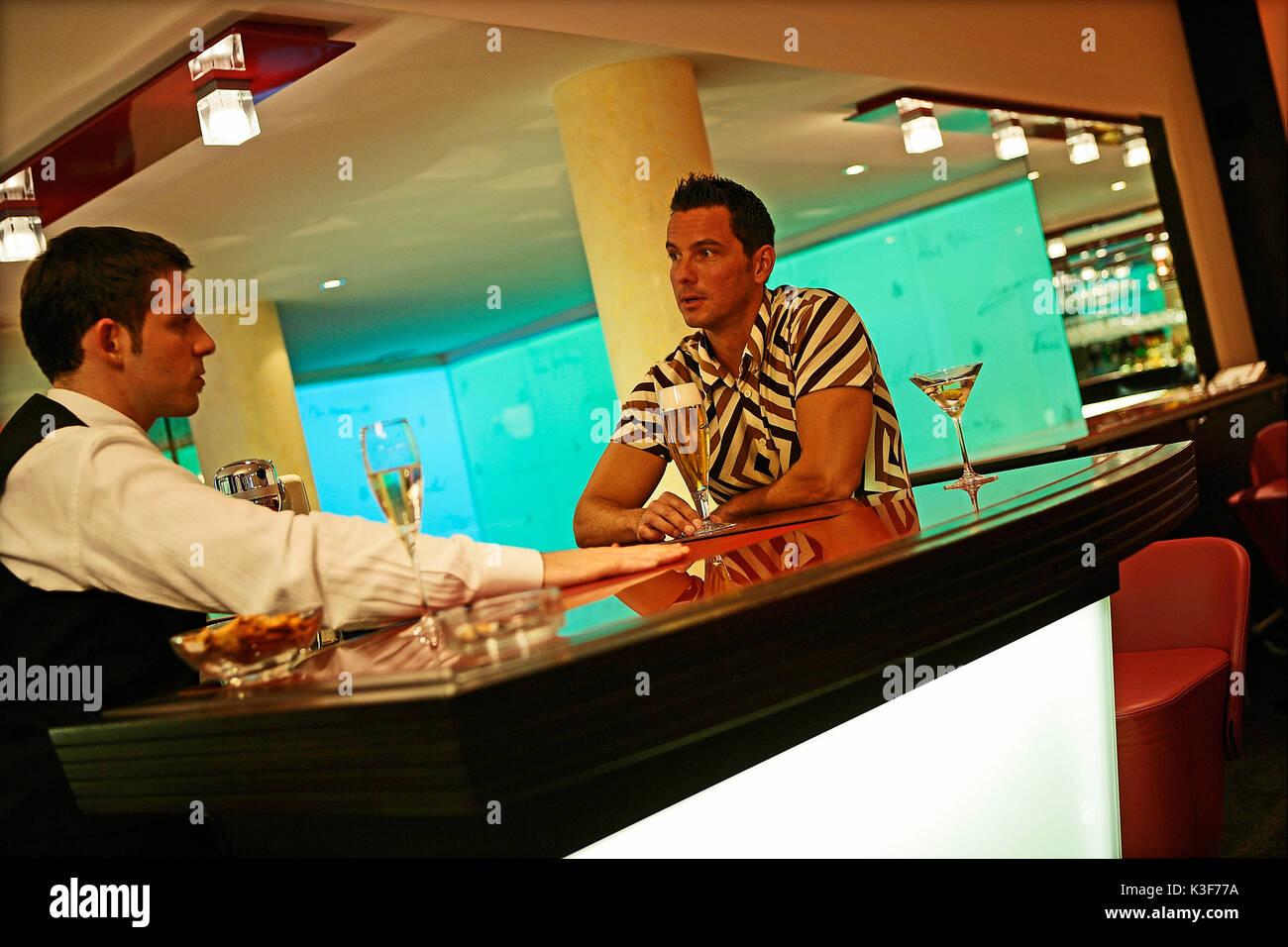 Man talks to barkeeper - Stock Image