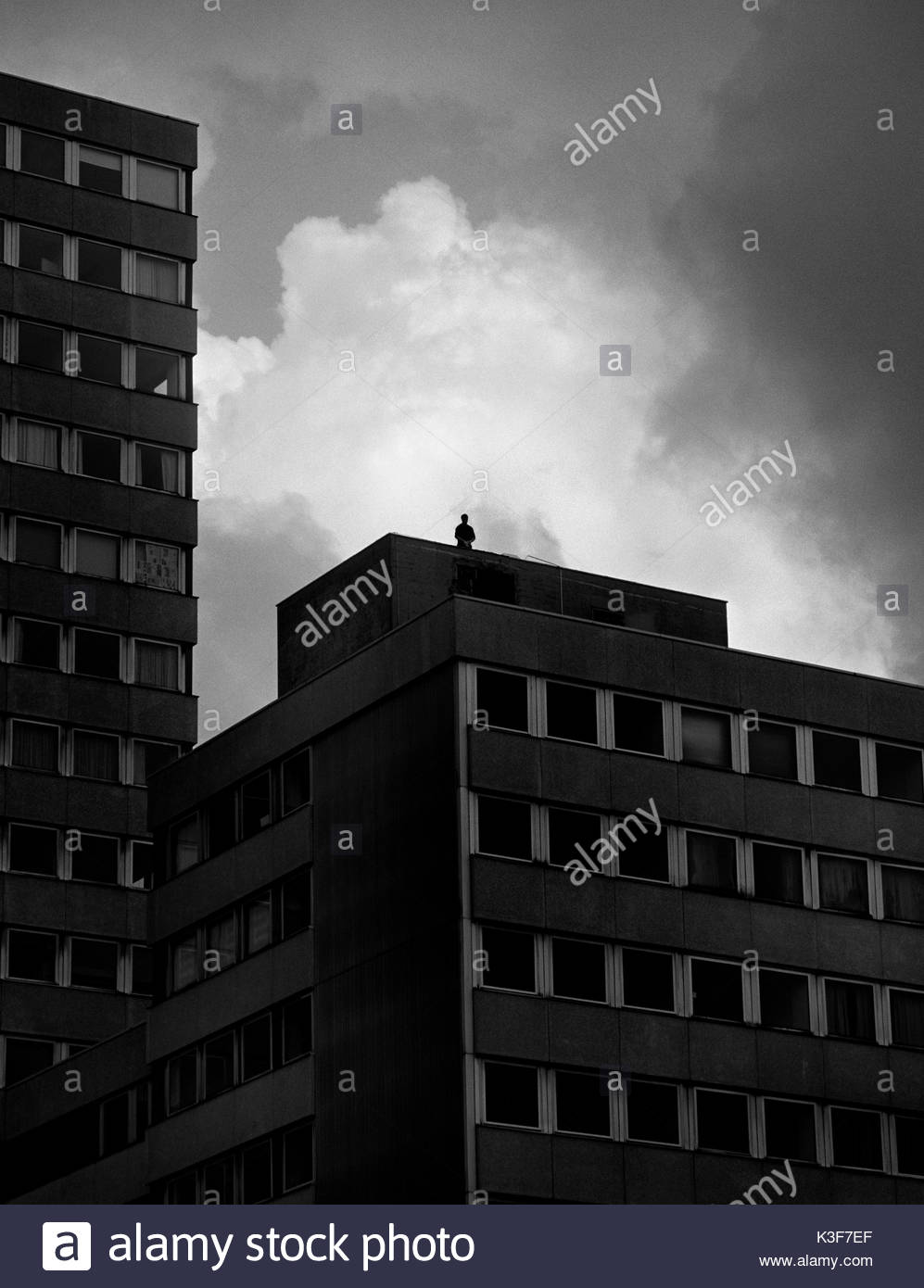 Silhouette of Man Standing on Roof of Building - Stock Image