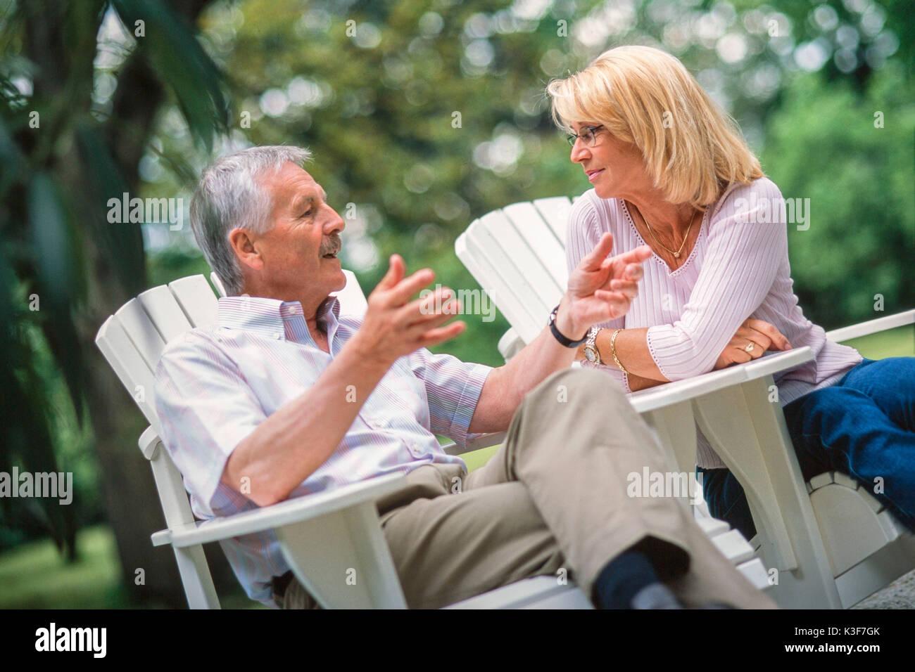 Couple talks in the garden - Stock Image