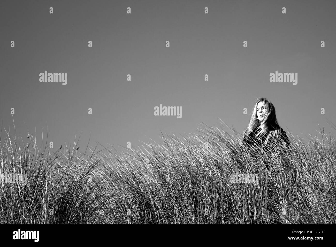 Portrait of Woman Standing Amongst Tall Grass - Stock Image