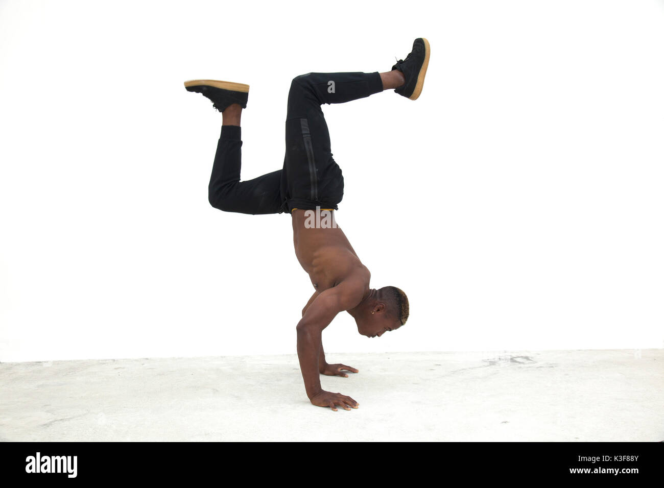 Young Adult Man Doing Handstand during Street Dance - Stock Image