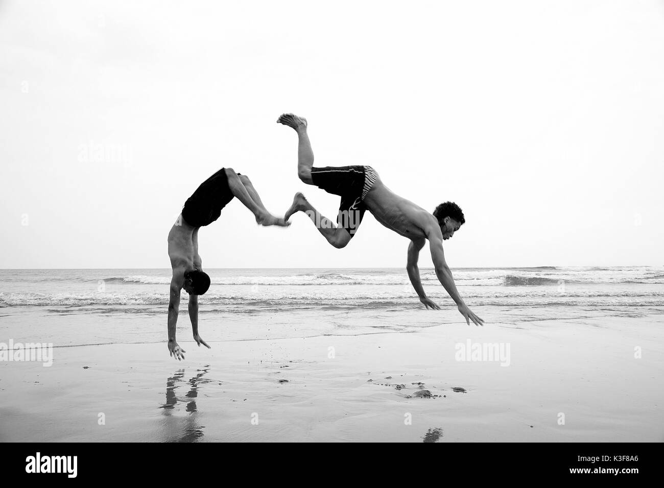 Two Young Men Jumping on Beach - Stock Image