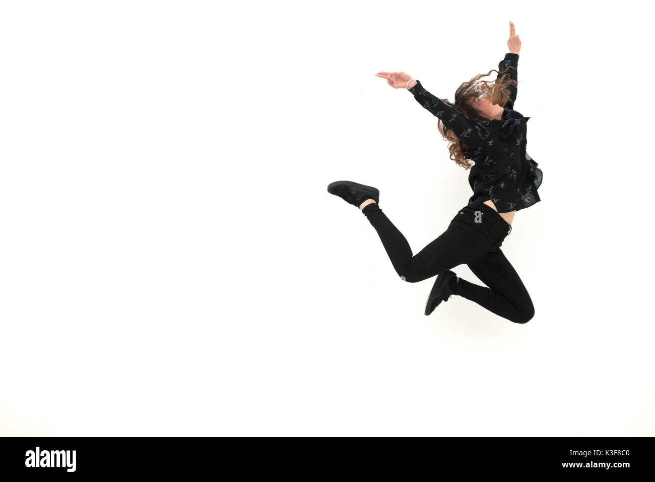 Young Adult Woman Leaping in Air During Dance Routine - Stock Image