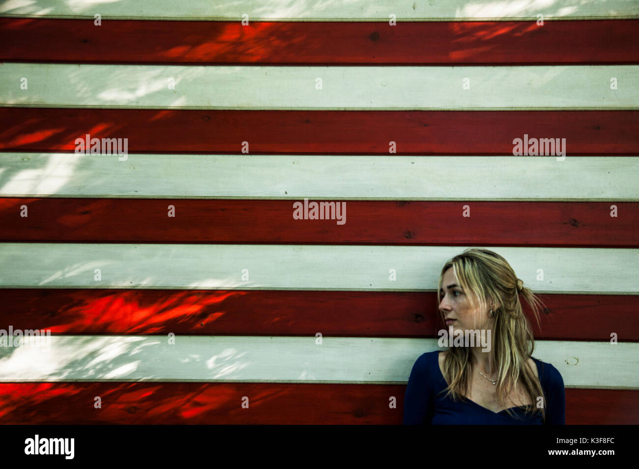 Profile Portrait of Sad Mid-Adult Woman Against Striped Wall - Stock Image