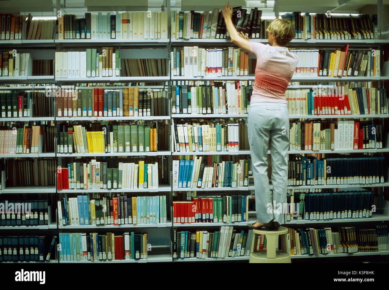 Woman searches book at the bookshelf of a library - Stock Image