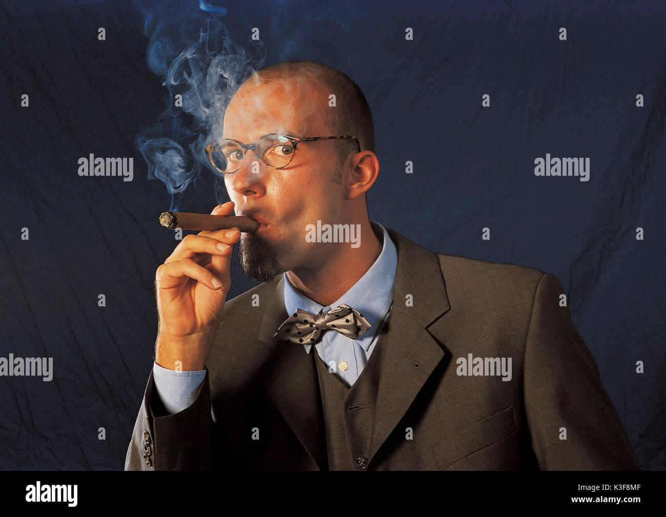 Cigar smoking man in suit with bow tie - Stock Image