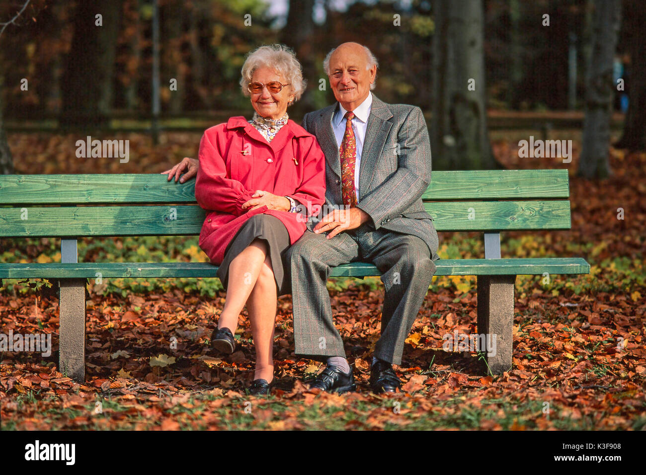 Senior citizen's couple sits together on a wooden bench at the wood Stock Photo