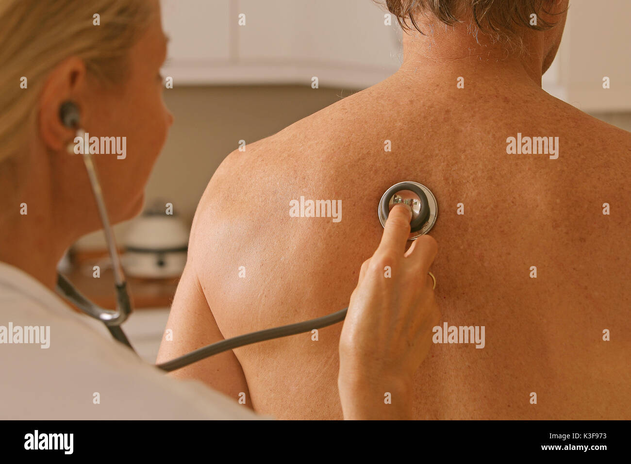 patient at stethoscope listens to doctor - Stock Image