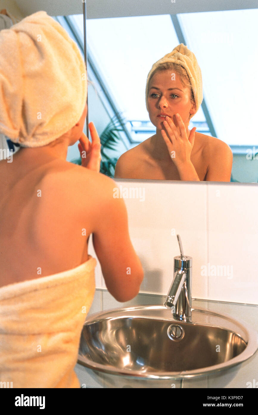 Woman considers herself at the mirror - Stock Image