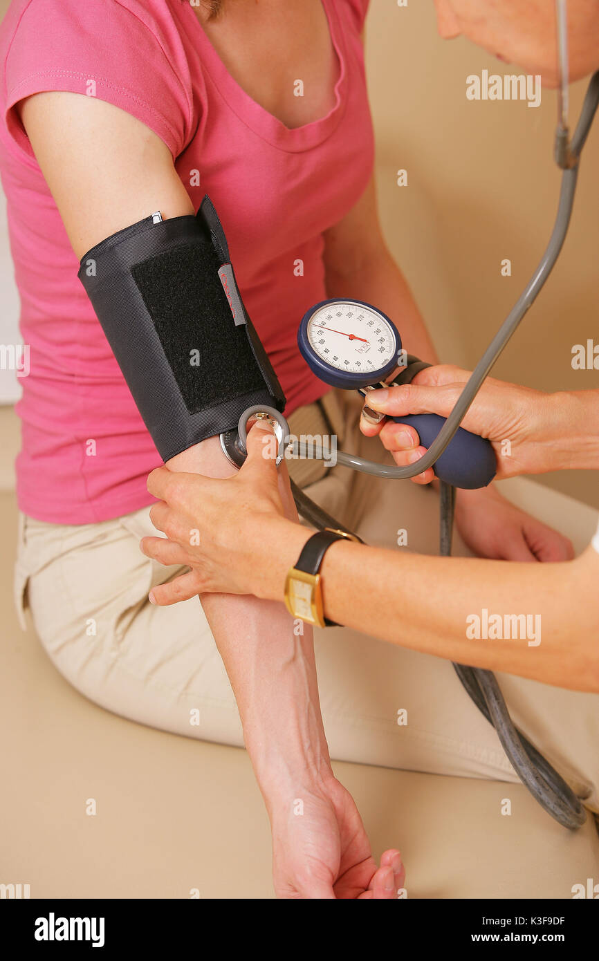 Doctor measures the blood pressure - Stock Image