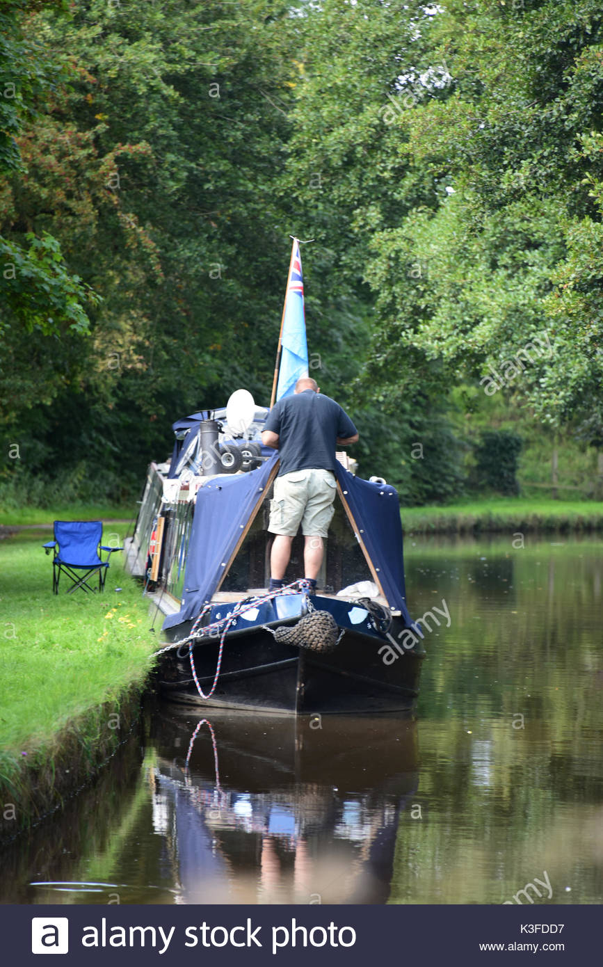Man working on his narrowboat moored on the Llangollen canal near Whitchurch, Shropshire - Stock Image
