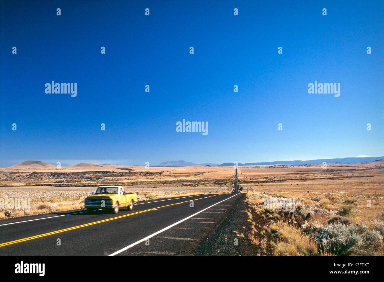 Car drives down a lonesome highway / street - Stock Image