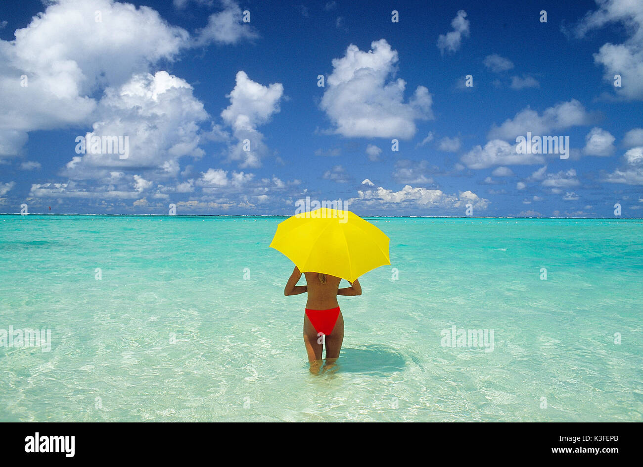 Young woman with red bikini and yellow sunshade - Stock Image