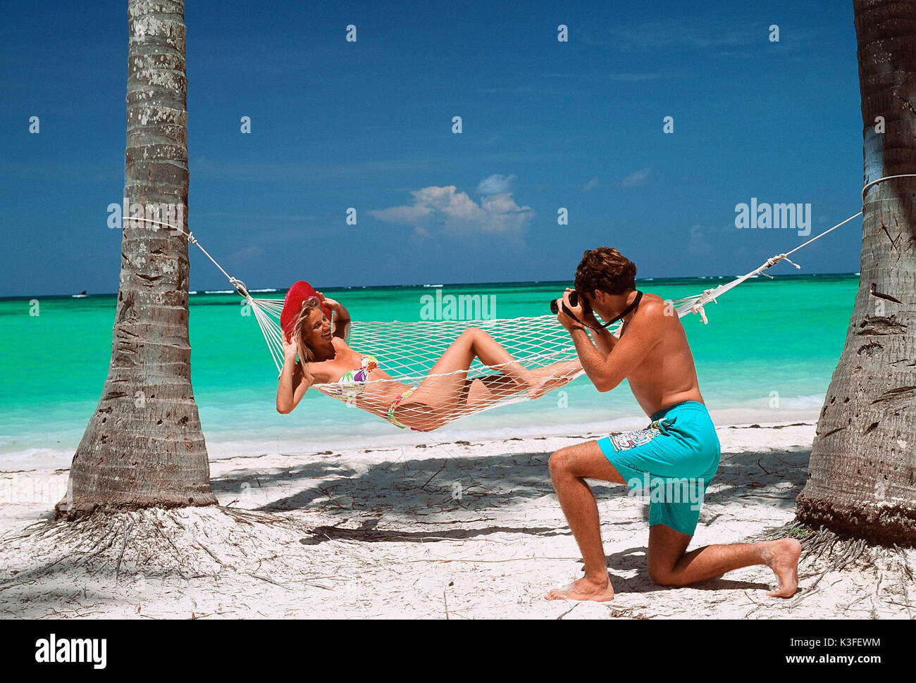 Man takes a photo of woman in hammock - Stock Image