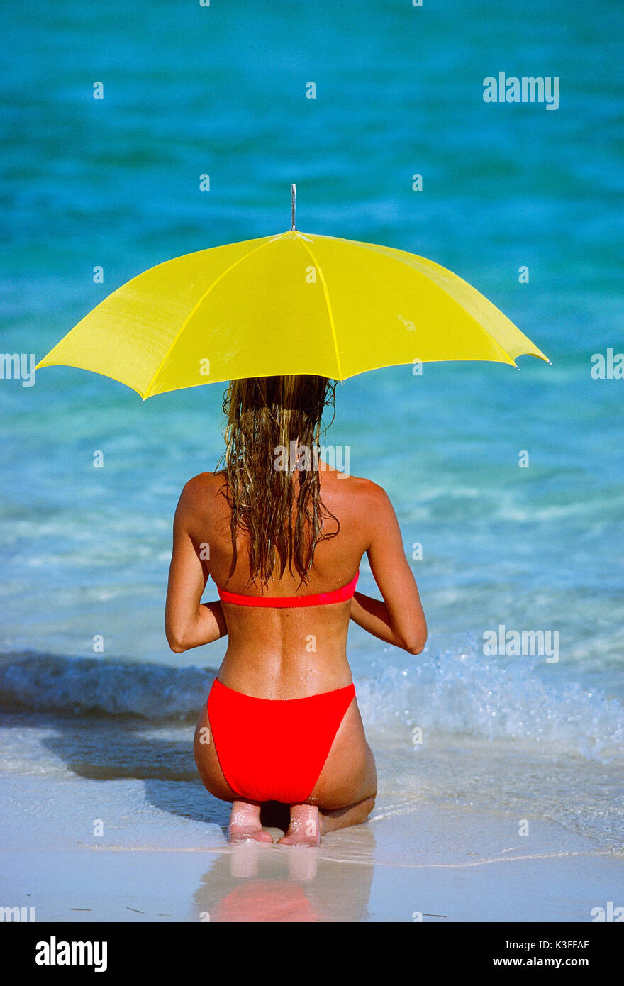 d8d3577412 Young woman with red bikini and yellow sunshade at the beach - Stock Image