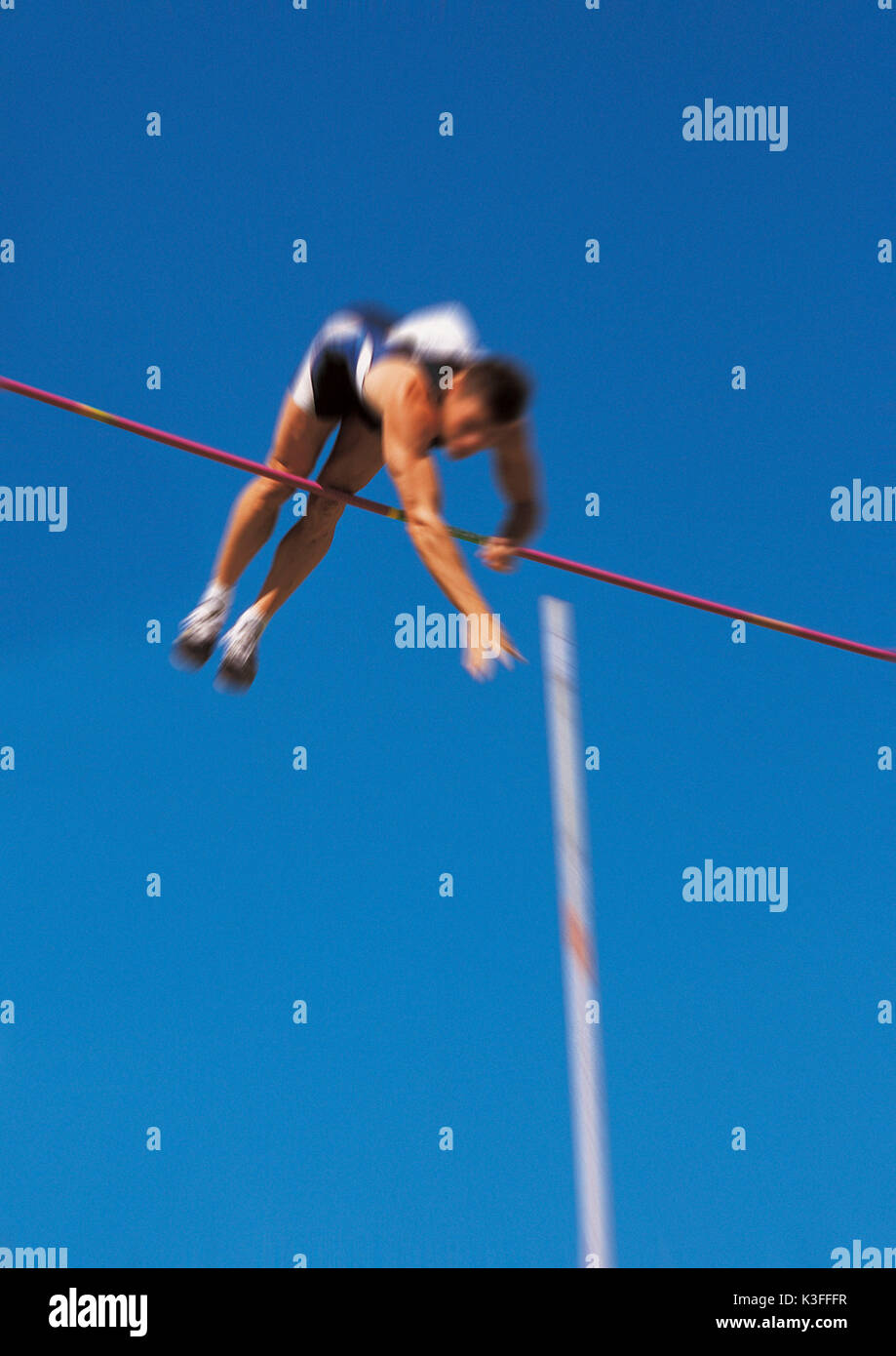 Man jumps over the bar close the pole vault - Stock Image