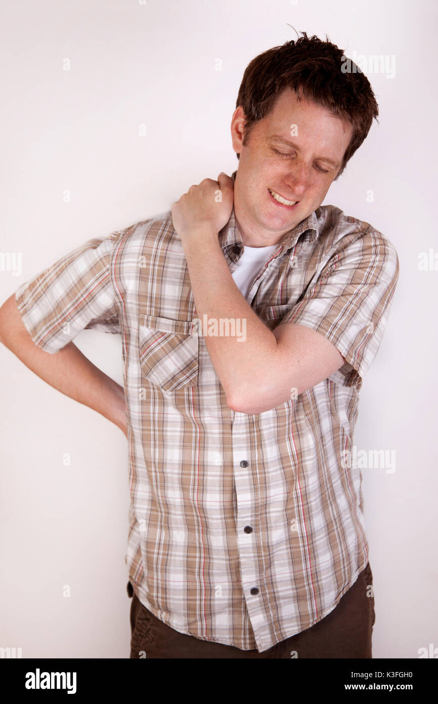 A man holding his neck or shoulder with the expression of pain on his face. - Stock Image
