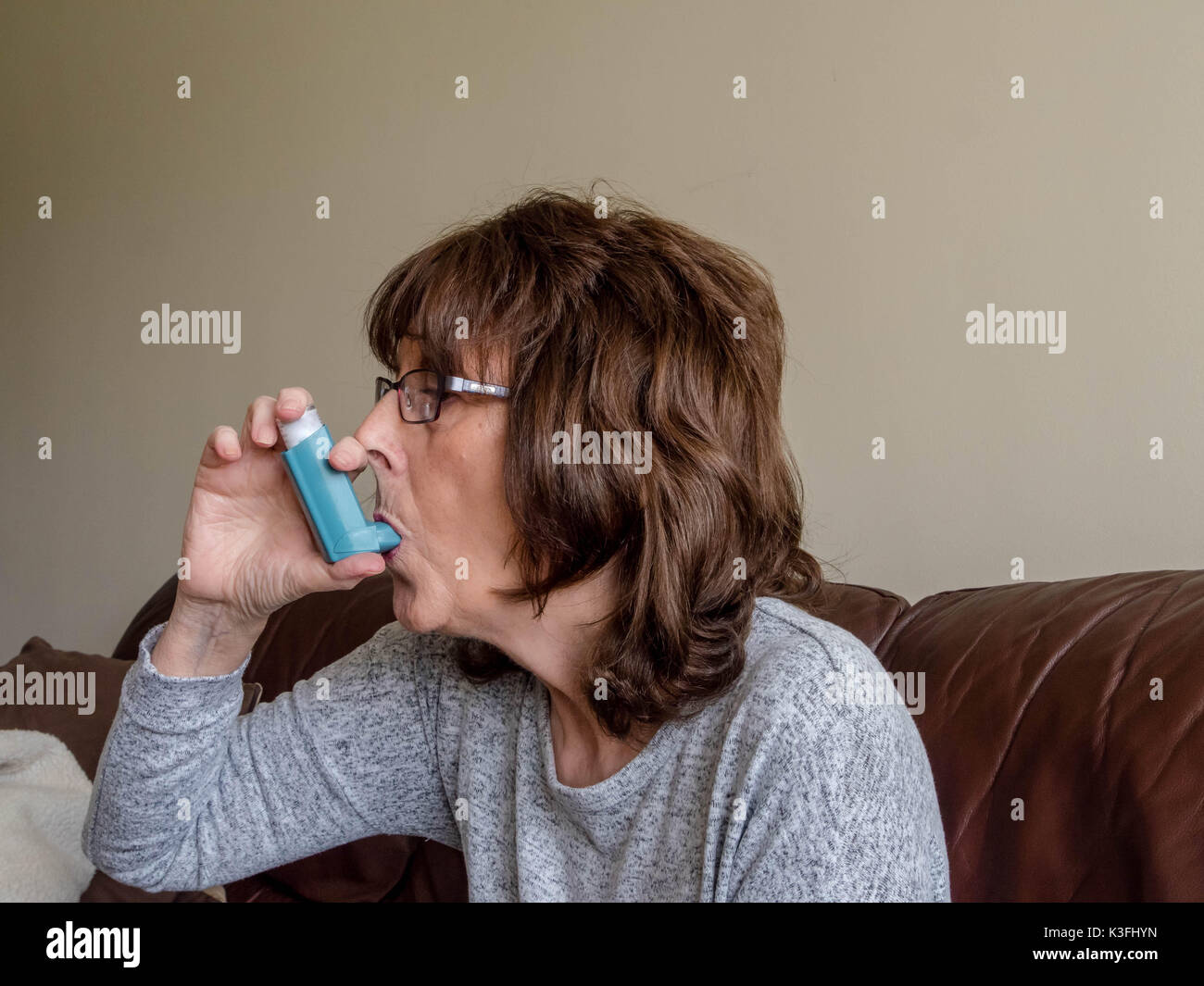 Mature senior lady using medical asthma aid to assisit with breathing - Stock Image
