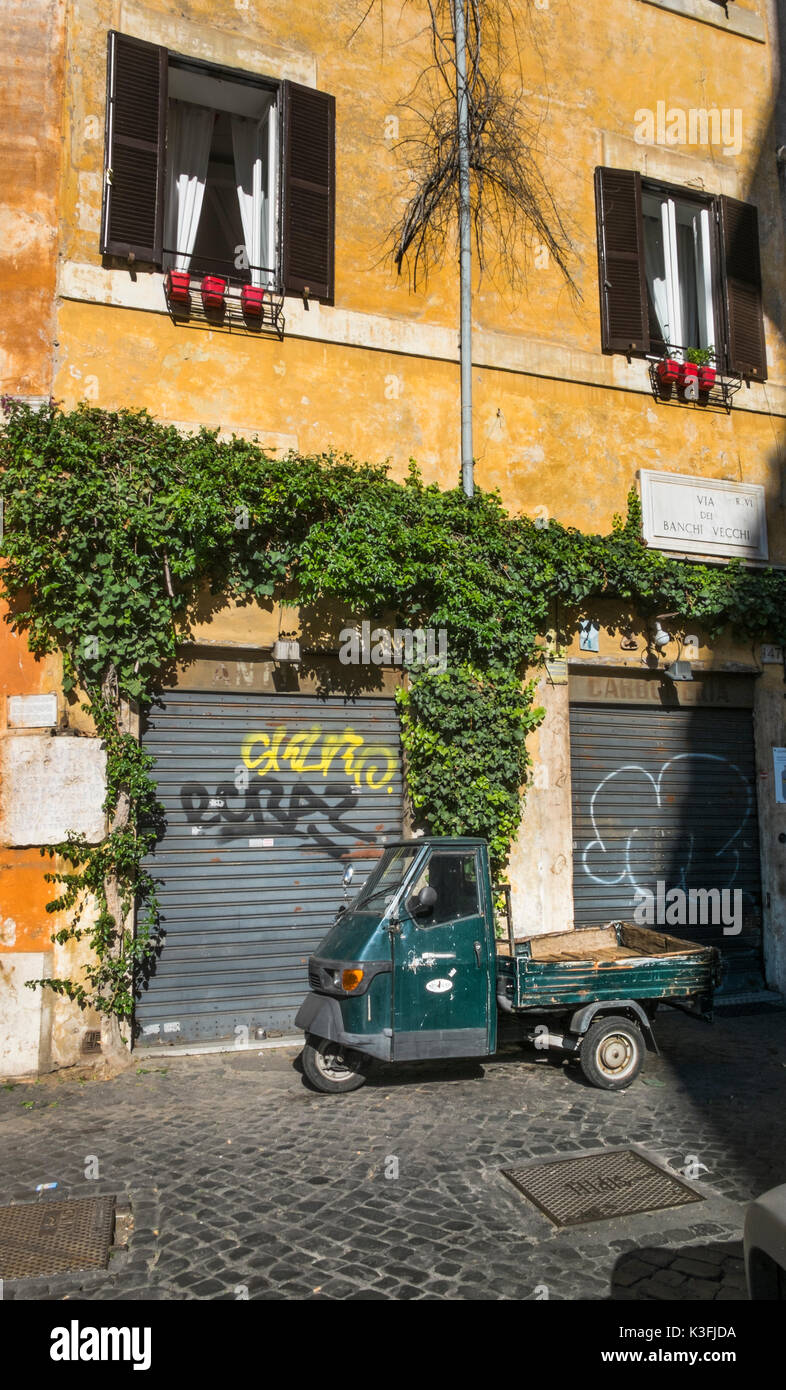 old  dark green piaggio ape three-wheeled commercial vehicle parked in front of a overgrown facade in the historic city center of rome - Stock Image